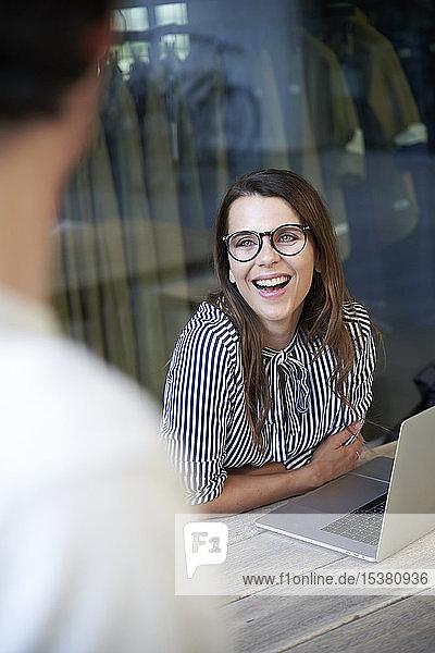 Glückliche Geschäftsfrau mit Laptop trifft Kollegin in der Stadt