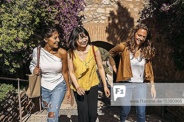 Drei glückliche Freundinnen laufen in der Stadt herum