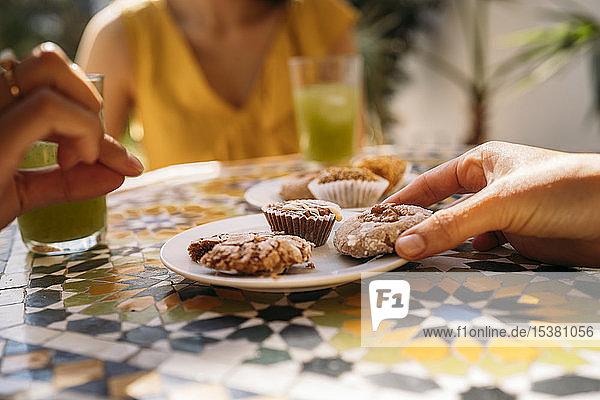 Close-up of woman taking a cookie from plate in a Moroccan cafe