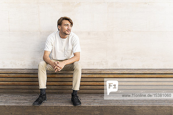 Porträt eines auf einer Holzbank sitzenden Mannes  der in die Ferne schaut