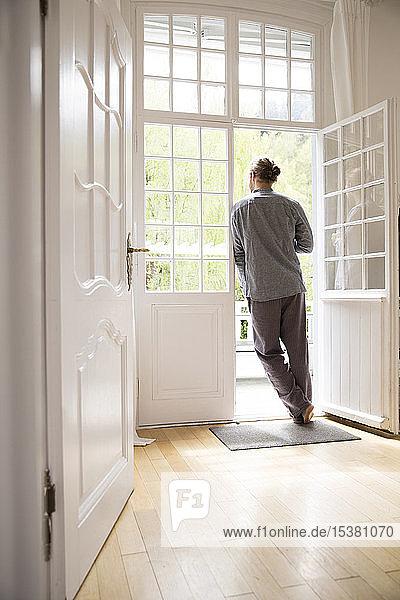 Junger Mann im Pyjama steht zu Hause an der Terrassentür
