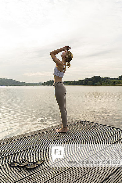 Young woman practicing yoga on a jetty at a lake