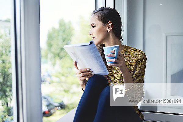 Young woman looking out the window while reading book at home