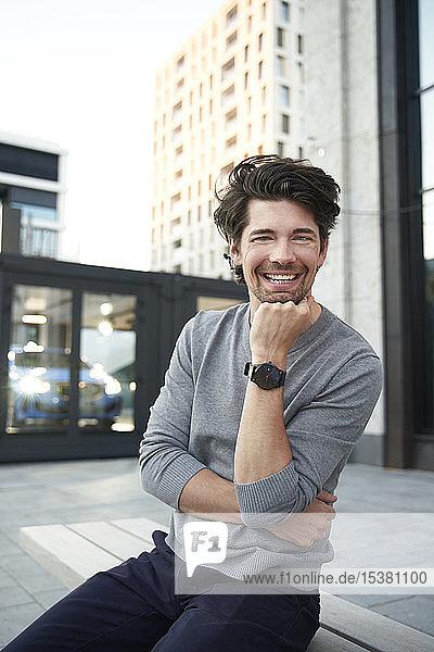 Porträt eines glücklichen Mannes in grauem Hemd  der auf einer Bank in der Stadt sitzt