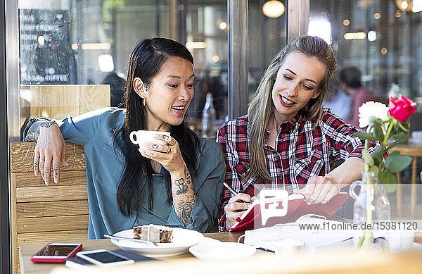 Zwei Frauen mit Buch in einem Cafe
