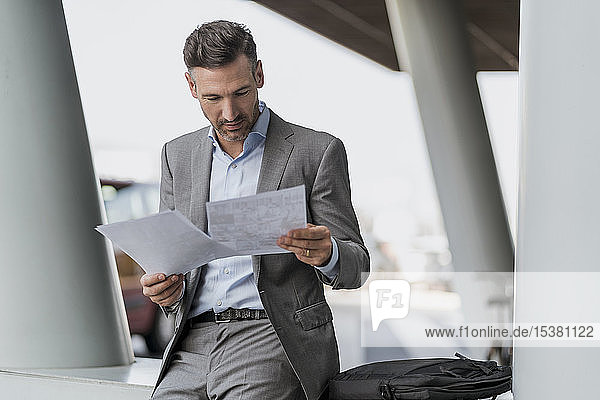 Geschäftsmann begutachtet Papiere im Freien