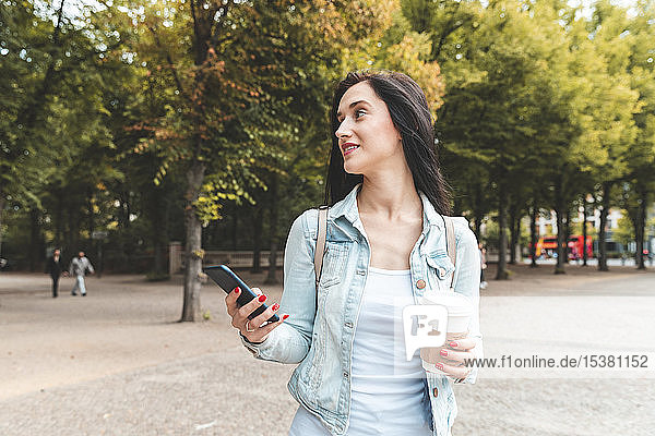 Young woman having a coffee and walking at a park  Berlin  Germany