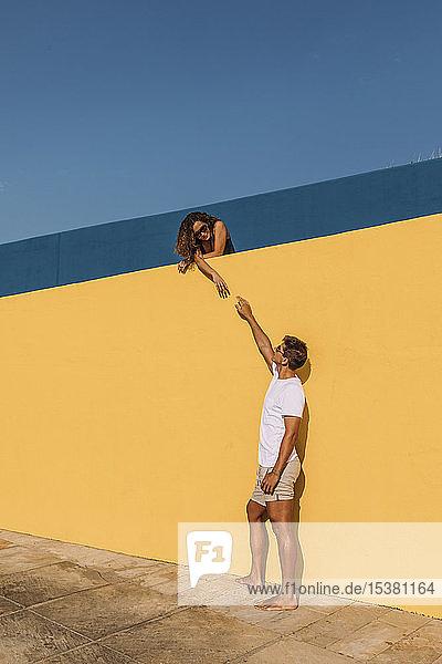 Junger Mann greift hinter einer gelben Mauer nach der Frau