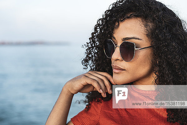 Beautiful woman  wearing sunglasses  standing at the sea  looking away