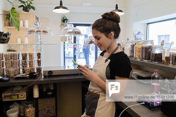 Young woman using cell phone behind the counter in a cafe