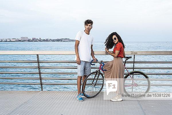 Junges Paar mit Fahrrad  stehend auf einer Brücke am Meer Junges Paar mit Fahrrad, stehend auf einer Brücke am Meer
