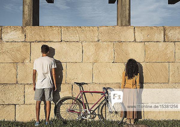 Junges Paar mit Fahrrad  vor der Wand stehend  Rückansicht Junges Paar mit Fahrrad, vor der Wand stehend, Rückansicht
