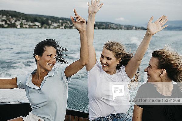 Glückliche Freundinnen haben Spaß bei einer Bootsfahrt auf einem See