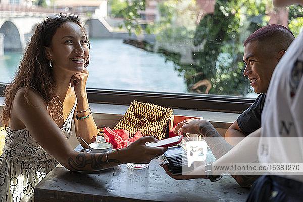 Porträt einer lächelnden Frau  die im Café mit einem Smartphone bezahlt
