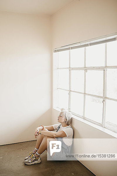 Young woman sitting on the floor in a room