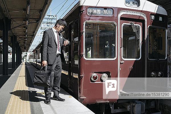 Junger Geschäftsmann auf einem Bahnsteig  der die Zeit überprüft