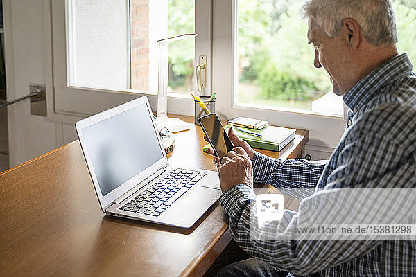 Senior man sitting in front of laptop using smartphone at home