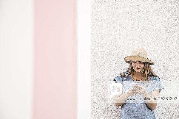 Frau  die mit einem Smartphone an einer Wand steht