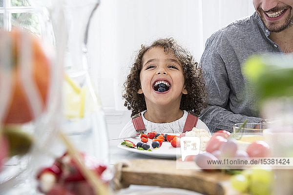 Verspielter Junge mit seinem Vater  der bei Tisch Blaubeeren isst