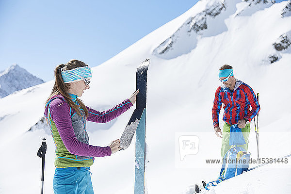 Couple of ski tourers removing pelt from ski in the mountains  Kuehtai  Tyrol  Austria