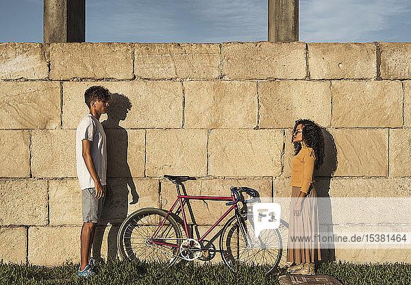 Junges Paar mit Fahrrad  vor der Wand stehend  von Angesicht zu Angesicht Junges Paar mit Fahrrad, vor der Wand stehend, von Angesicht zu Angesicht