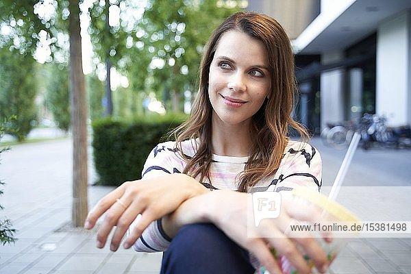 Lächelnde Frau  die in der Stadt eine Pause macht und eine Tasse hält