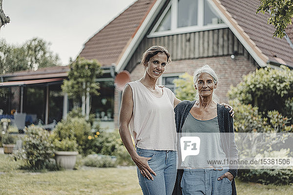Mother and daughter standing in garden  inf ront of their house