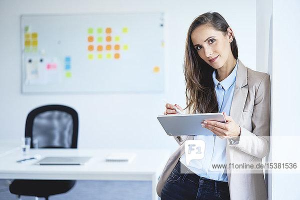 Junge Geschäftsfrau lächelt in die Kamera  während sie im Büro ein Tablet benutzt