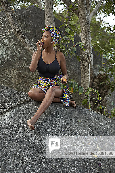 Young woman siting on a rock eating a fruit
