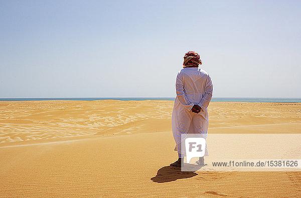 Beduine in Nationaltracht in der Wüste stehend  Rückansicht  Wahiba Sands  Oman