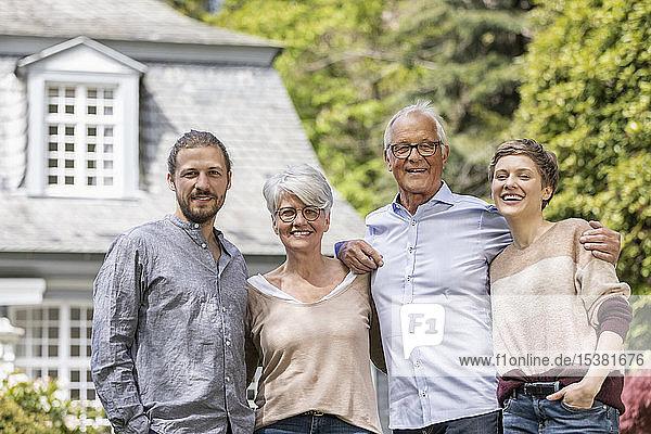 Glückliches älteres Ehepaar mit erwachsenen Kindern  die im Garten ihres Hauses stehen