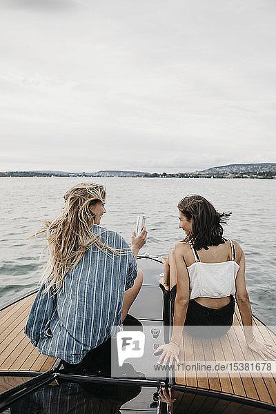 Glückliche Freundinnen bei einer Bootsfahrt auf einem See