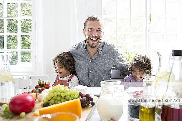 Glücklicher Vater mit zwei Söhnen beim Mittagessen zu Hause