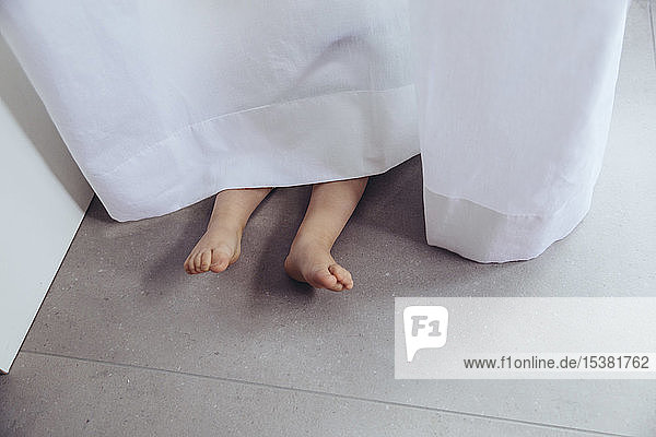 Legs and feet of little boy  hiding behind curtain