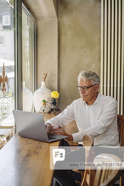 Leitender Geschäftsmann benutzt Laptop in einem Café
