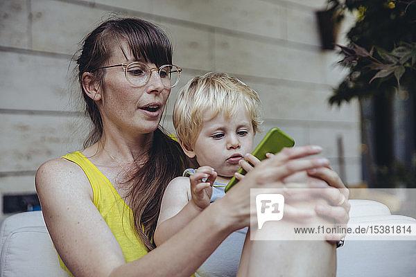 Kleiner Junge sitzt auf dem Schoß der Mutter und schaut auf das Smartphone