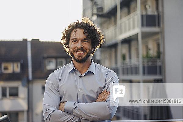 Porträt eines lächelnden Geschäftsmannes auf der Dachterrasse