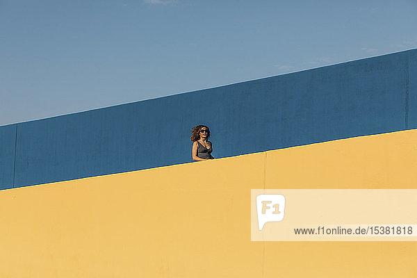 Junge Frau hinter einer gelben Mauer