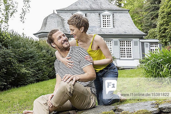 Happy woman embracing man on a wall in garden of their home