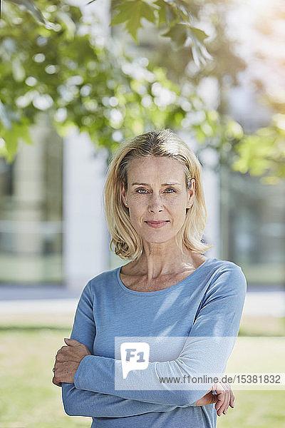 Portrait of confident blond woman in a park