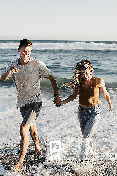 Happy young couple running at the seashore