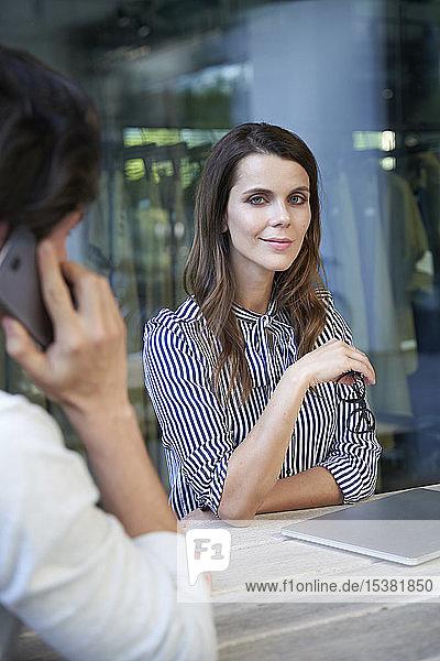 Porträt einer selbstbewussten Geschäftsfrau und eines Mannes am Handy in der Stadt
