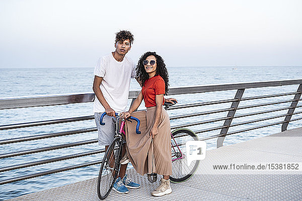 Young couple with bicycle  standing on bridge by the sea
