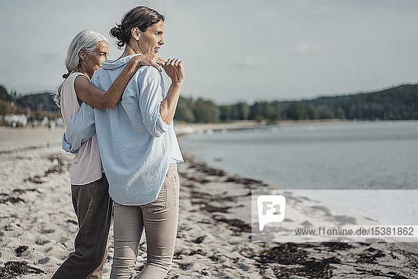 Mutter und Tochter verbringen einen Tag am Meer  umarmen sich am Strand