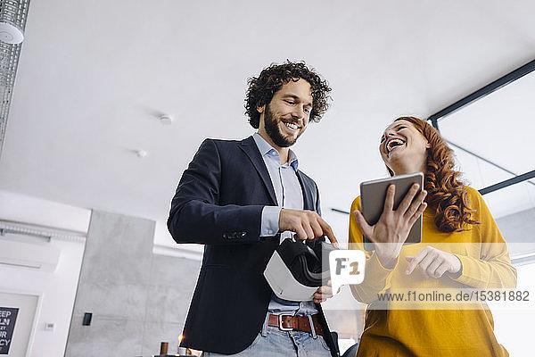 Glücklicher Geschäftsmann und Geschäftsfrau mit VR-Brille und Tablett im Büro