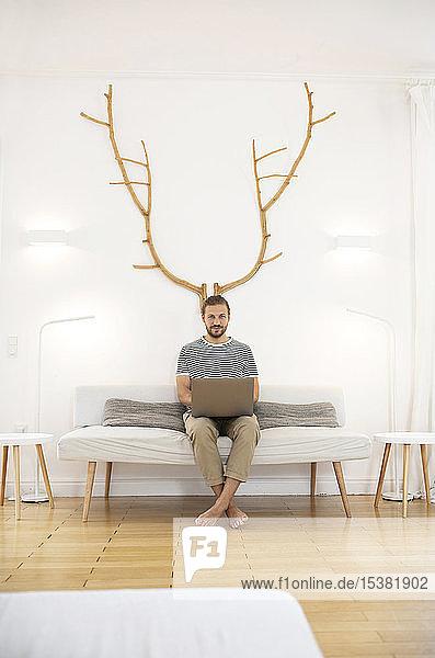 Junger Mann benutzt Laptop zu Hause