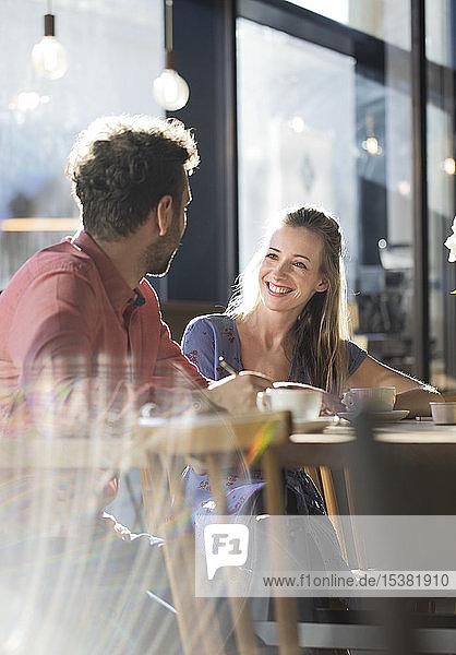 Lächelnde Frau und Mann unterhalten sich am Tisch in einem Café
