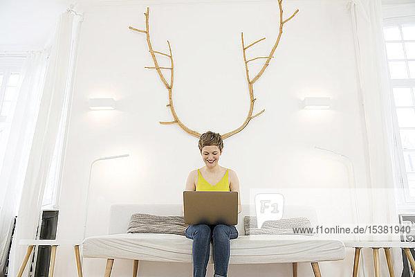 Lächelnde Frau benutzt Laptop zu Hause