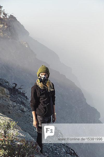 Junge Frau mit Atemschutzmaske steht am Rande des Vulkans Ijen  Java  Indonesien