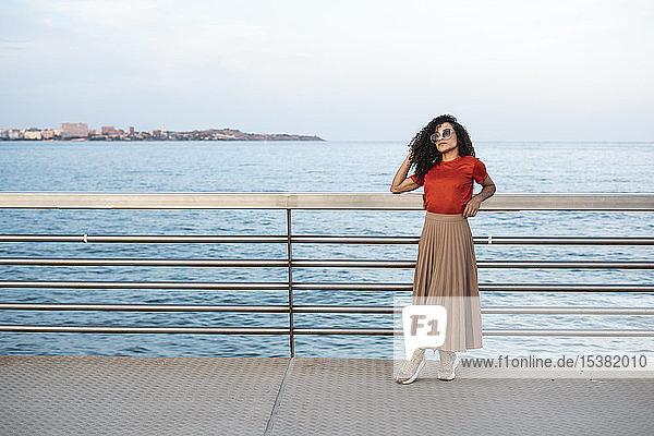 Schöne Frau  Sonnenbrille tragend  an der Reling am Meer lehnend